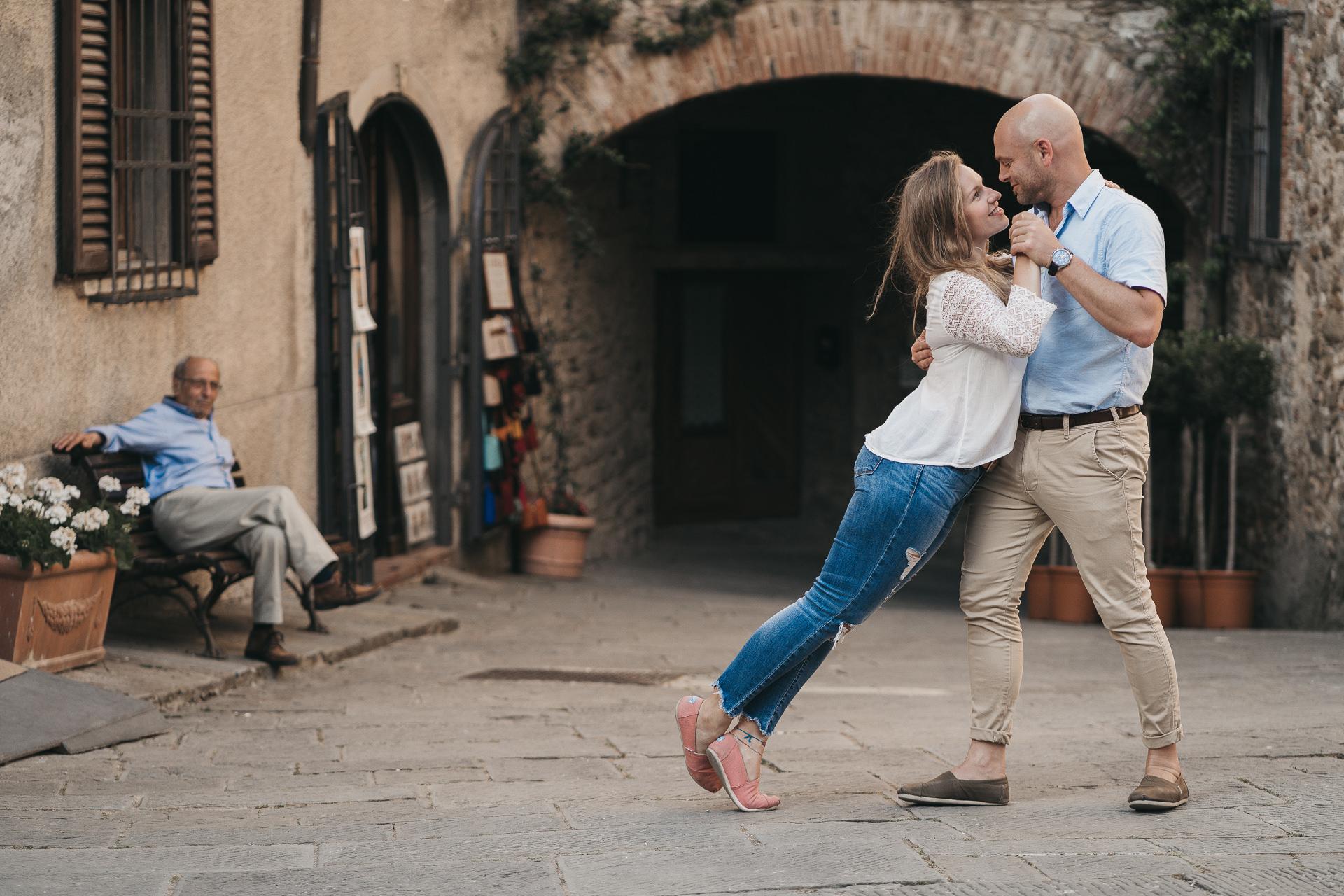 Paar tanzt in den Gassen Italiens - Paarfotoshooting in der Toskana - Tanzendes Pärchen in Castelina Italien - Chris Reuter Hochzeitsfotograf