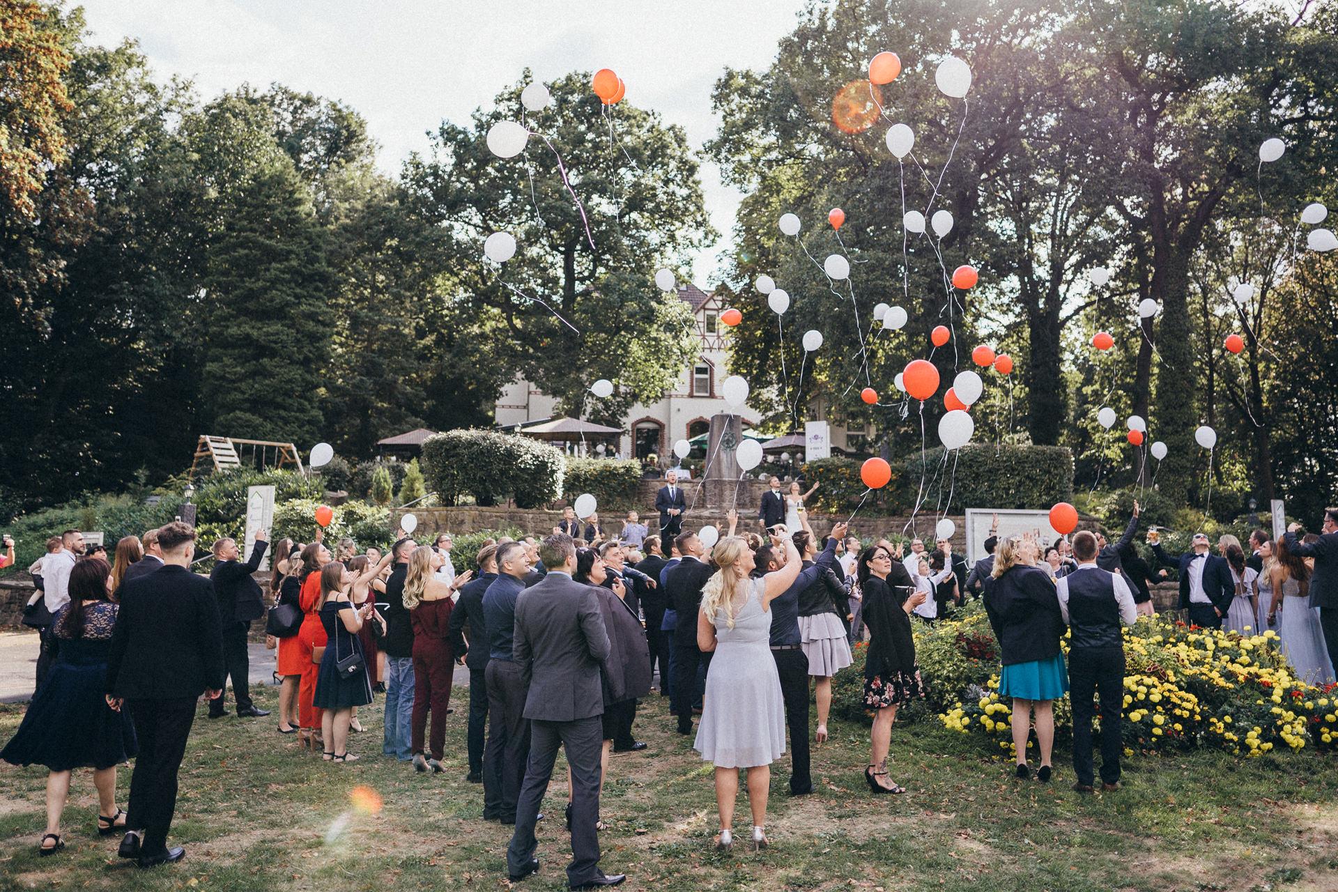 Hochzeitsgesellschaft lässt Ballons steigen - Rote und weiße Luftballons zur Hochzeitsfeier - Hochzeitsreportage in Dortmund - Chris Reuter Hochzeitsfotograf