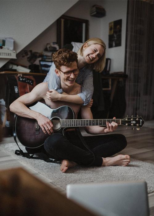 Pärchen spielt zusammen Gitarre und albert herum - Paarfotoshooting in Köln - Chris Reuter Hochzeitsfotograf